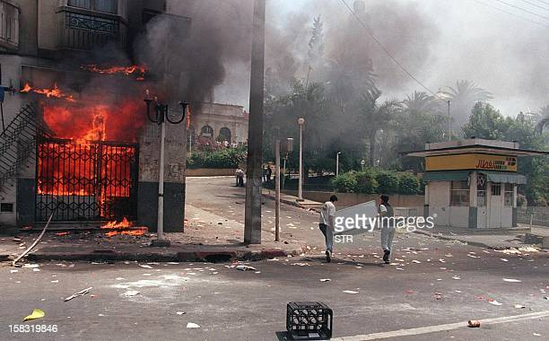 Two youths run with a refrigerator past a burning building 26 June after several hours of violence against state offices following the assassination...