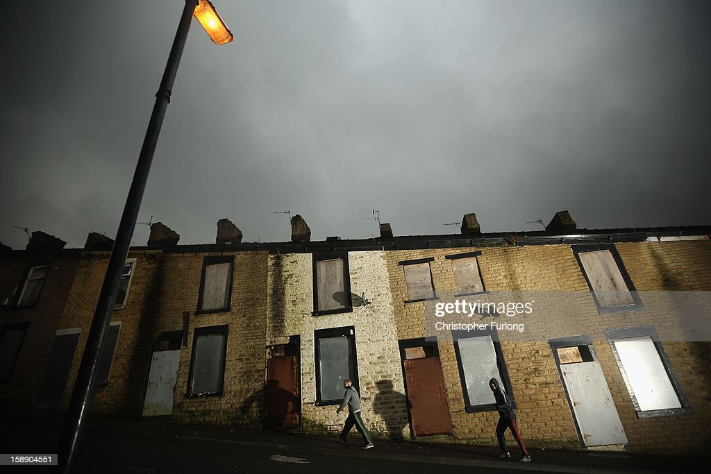 Two youths walk past empty former council houses that line a street in the Lancashire town of Accrington which are waiting to be modernised by private developers on January 3, 2013 in Accrington, England. There are estimated to be 850,000 empty homes in the United Kingdom even though local councils still have long waiting lists for housing. The terraced houses were due to be rejuvenated by Accrington council but the project was put on hold when the government cut a housing regeneration project.