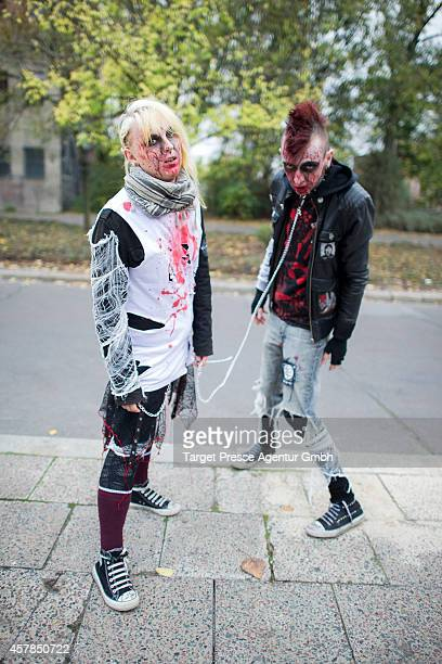 Two zombie enthusiast walk over the Alexanderplatz as part of a flashmob on October 25 2014 in Berlin Germany Over 150 participants dressed as...