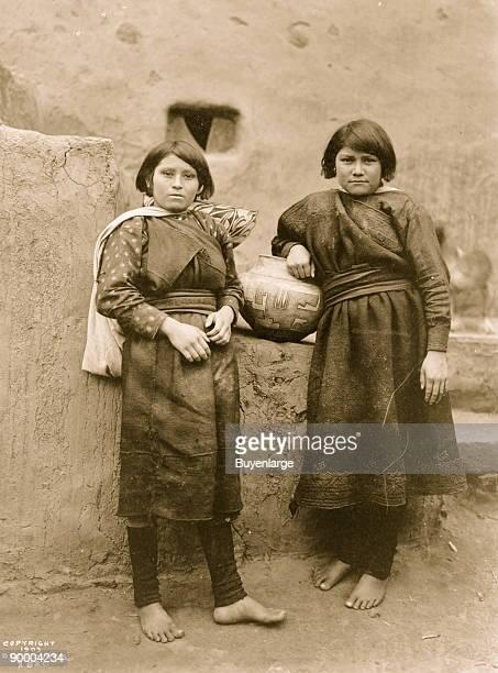 Two Zuni girls standing in front of pueblo buildings