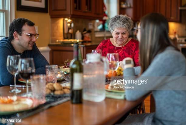 famille de deux générations, la mère de 65 ans avec des enfants adultes, se sont réunis et ont le dîner de noel - 30 34 years photos et images de collection