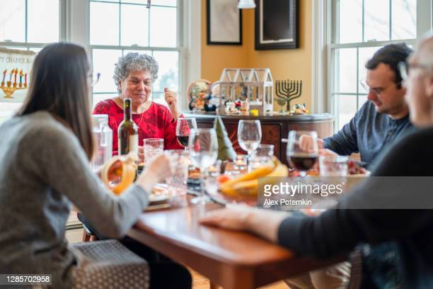 two-generation multicultural family, the senior couple with adult kids, gathered together and have the holiday dinner in the living room decorated for both christmas and hanukkah. - judaism stock pictures, royalty-free photos & images