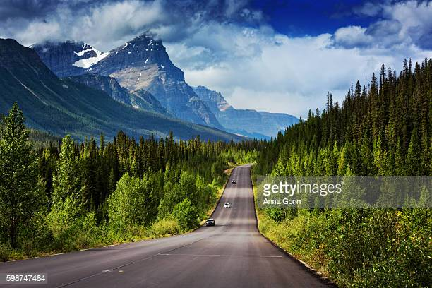 two-lane famous icefields parkway between lake louise and jasper, alberta, with snowcapped mountains looming above in summer - paisajes de canada fotografías e imágenes de stock