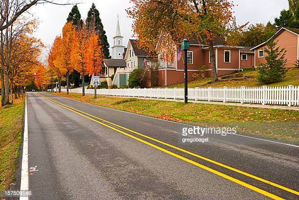 two-lane highway through small american town - double yellow line stock photos and pictures