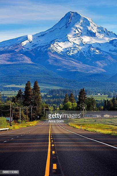 two-lane road leading straight toward snowcapped mount hood on spring afternoon, oregon - hood river stock pictures, royalty-free photos & images