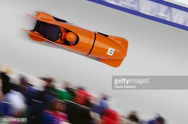 Two-man bobsled racing down track (blurred motion)