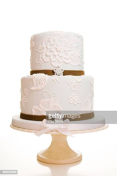 two-tiered white wedding cake with brown ribbon - wedding cake foto e immagini stock