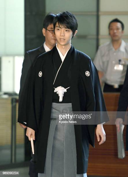 Twotime figure skating Olympic gold medalist Yuzuru Hanyu arrives at the premier's office in Tokyo on July 2 to attend a ceremony to receive the...