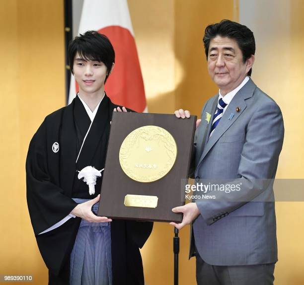 Twotime figure skating Olympic gold medalist Yuzuru Hanyu poses for photos with Japanese Prime Minister Shinzo Abe as he receives the People's Honor...