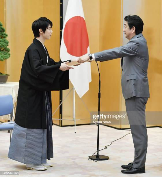 Twotime figure skating Olympic gold medalist Yuzuru Hanyu receives a People's Honor Award certificate from Japanese Prime Minister Shinzo Abe at a...