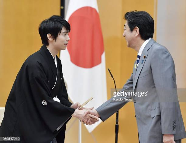 Twotime figure skating Olympic gold medalist Yuzuru Hanyu shakes hands with Japanese Prime Minister Shinzo Abe after receiving the People's Honor...