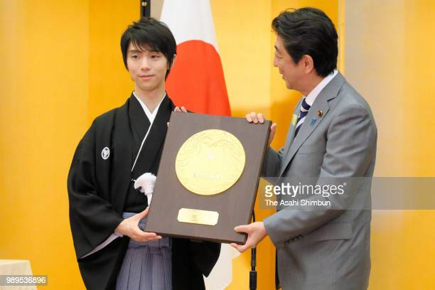 Twotime Olympic figure skating Men's Singles gold medalist Yuzuru Hanyu receives the plaque from Japanese Prime Minister Shinzo Abe during the...