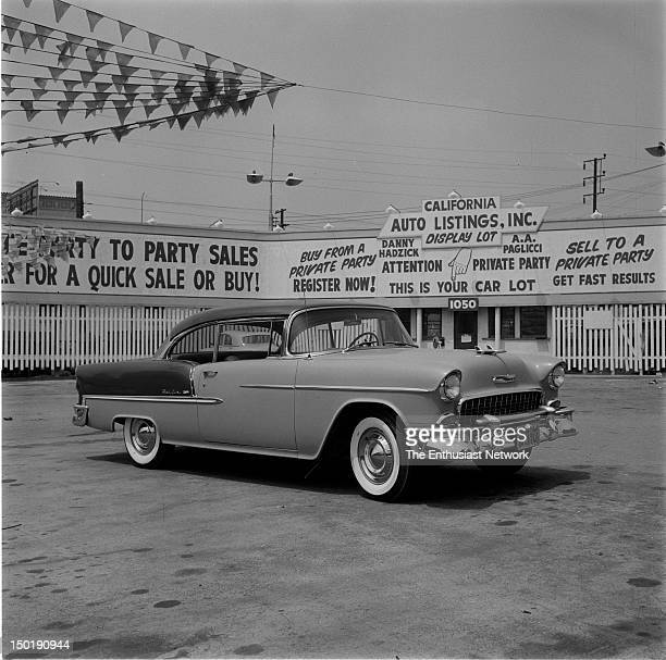 Twotone 1955 Chevrolet Bel Air in usedcar lot with banners and signs Whitewall tires California Auto Listings Incorporated Display Lot