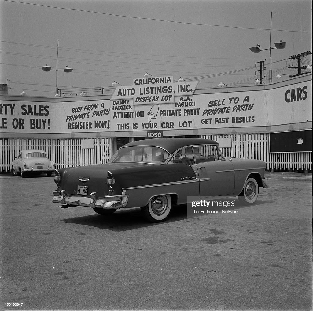 Two Tone 1955 Chevrolet Bel Air In Used Car Lot With Banners And News Photo