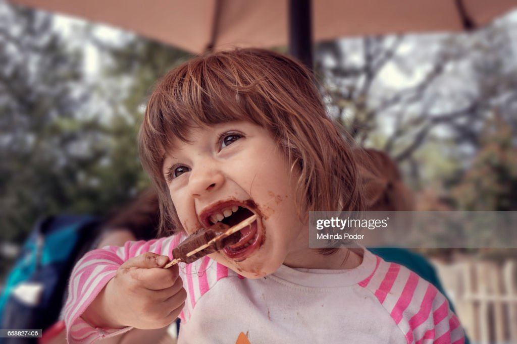 Two-year old girl eating a popsicle : Stock-Foto