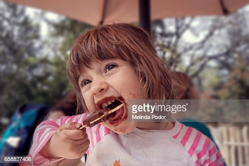 Two-year old girl eating a popsicle