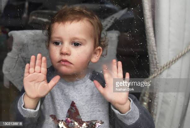 Two-year-old Blossom Walker, who is the photographer's niece looks through a window at her Grandparents home on February 20, 2021 in Biddulph,...