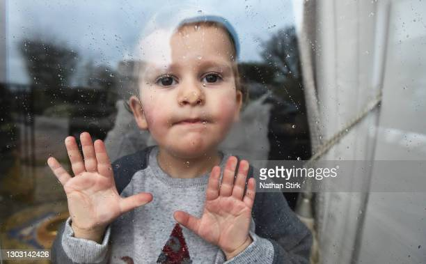 Two-year-old Blossom Walker, who is the photographer's niece looks through a window at her her Grandparents home on February 20, 2021 in Biddulph,...