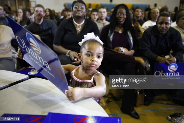 Twoyearold Brooklynn Smith of Waterloo Iowa holds a Barack Obama campaign sign while attending his campaign appearance with her parents at the...