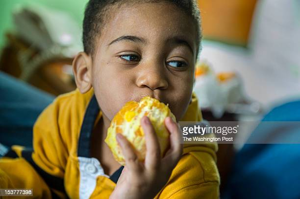 Twoyearold Cameron Newsome enjoys an orange from the hotel breakfast bar Thursday October 4 2012 in Leesburg VA His family has been on the streets...