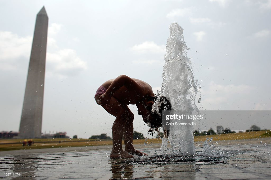 Two-year-old Carmen Brumos of Valencia, Spain, lowers her head into a jet of water near the Washington Monument on the National Mall July 8, 2010 in Washington, United States. Temperatures on the East Coast reached the mid-90s by midday on Thursday, showing a break in the 100-degree days from earlier in the week.