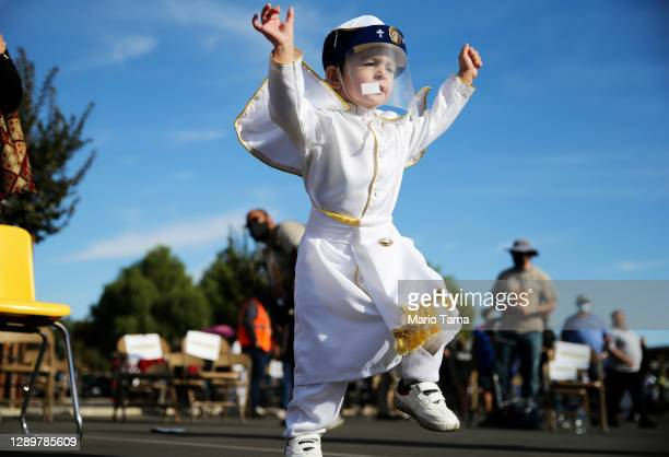 Two-year-old Fabian Acuna dances wearing a face shield following the traditional procession and Mass in honor of Our Lady of Guadalupe at San Gabriel...