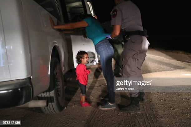Two-year-old Honduran asylum seeker cries as her mother is searched and detained near the U.S.-Mexico border on June 12, 2018 in McAllen, Texas. The...