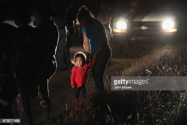 A twoyearold Honduran stands with her mother after being detained by US Border Patrol agents near the USMexico border on June 12 2018 in McAllen...