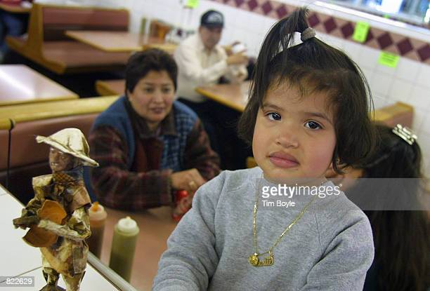 Twoyearold Leslie Carbajal poses for a photograph as her mother and aunt await their lunch in the restaurant of the Carniceria Aguascalientes grocery...