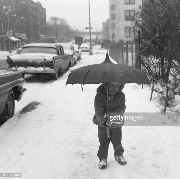 Two-year-old Mary Olskey carries an umbrella as she takes tentative steps on the snow in the Astoria neighbourhood of the Queens borough of New York...