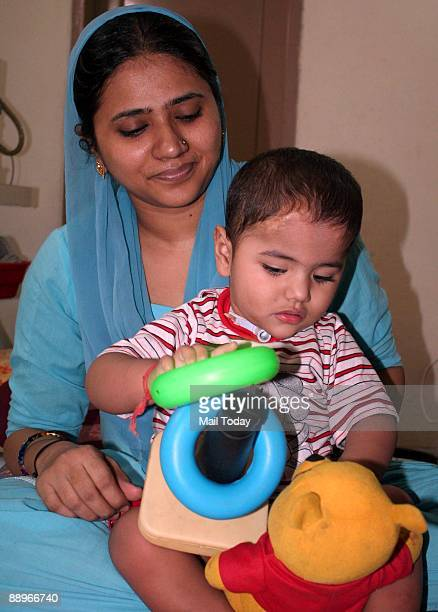 Twoyearold Muaaz Ahmed who is suffering from a rare respiratory disorder Ondine's Curse plays with his mother at his residence in Gurgoan Haryana on...