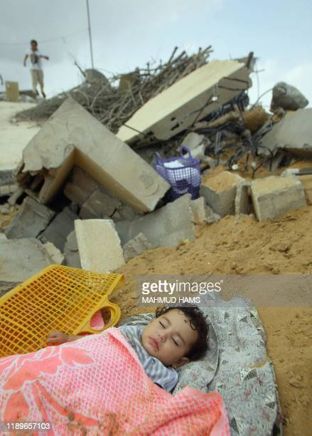 Two-year-old Palestinian Wafaa al-Bahri sleeps among the rubble of her destroyed home in Beit Lahia in the northern Gaza Strip 11 September 2004. The...
