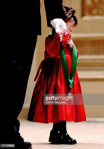 Two-year-old Patricia Smith holds her father's gloved hand 04 December 2001 in New York after accepting the New York Police Department's highest...