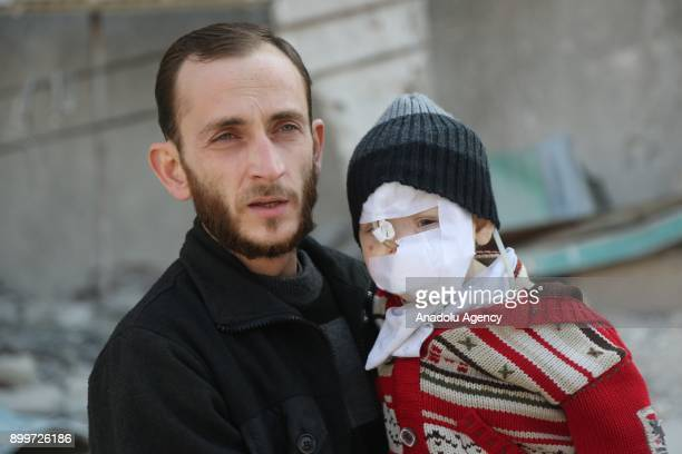 Twoyearold Syrian baby Kasim and his father Mohammad Kahveci are seen in front of a debris of a building in besieged Damascus suburb of Eastern...