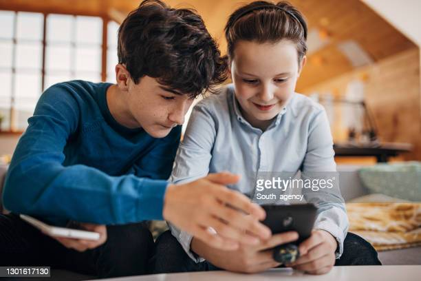 twp boys using mobile phones at home - children only stock pictures, royalty-free photos & images