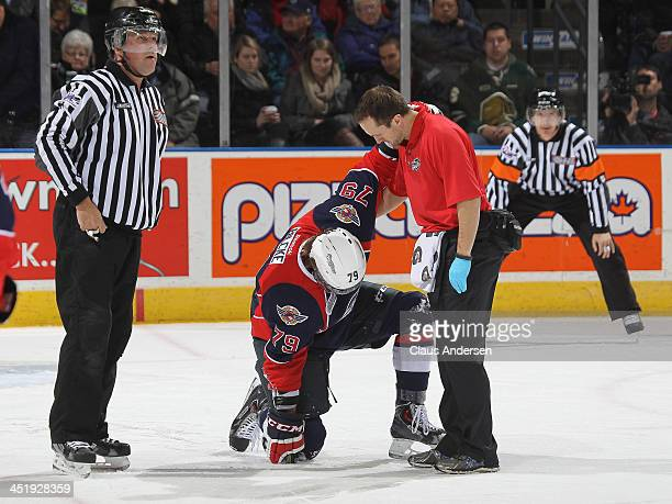 Ty Bilcke of the Windsor Spitfires is tended to by Joey Garland during play stoppage against the London Knights in an OHL game at the Budweiser...