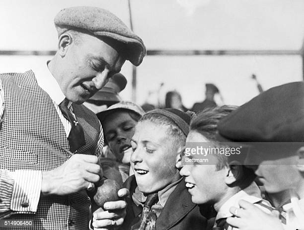 Ty Cobb signing autograph for young fans.