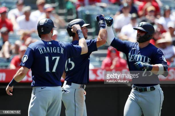 Ty France of the Seattle Mariners celebrates his three run home run with Mitch Haniger and Dylan Moore during the fifth inning against the Los...