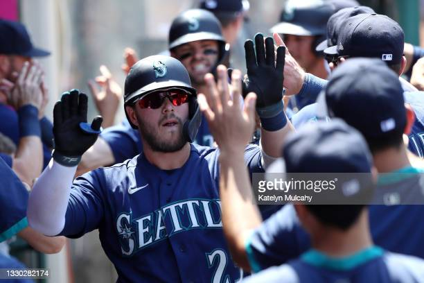 Ty France of the Seattle Mariners celebrates his three run home run with teammates in the dugout during the fifth inning against the Los Angeles...