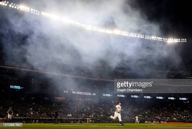 Ty France of the Seattle Mariners runs to first base as smoke clears from fireworks that fired after a home run by Mitch Haniger of the Seattle...