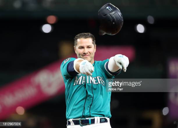 Ty France of the Seattle Mariners throws his helmet to celebrate after hitting a walk-off double in the ninth inning against the Houston Astros at...