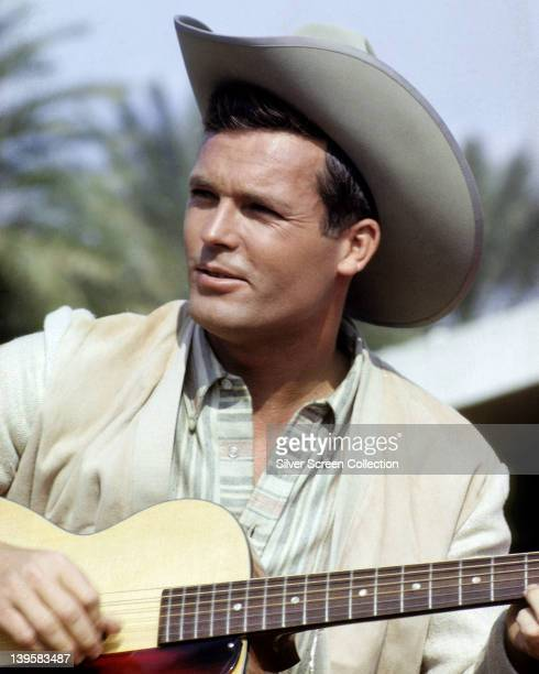 Ty Hardin US actor bare chested sitting on the beach circa 1965