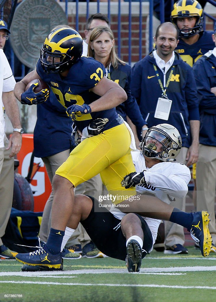 Ty Isaac #32 of the Michigan Wolverines is tackled by Rick Gamboa #32 of the Colorado Buffaloes during the second half at Michigan Stadium on September 17, 2016 in Ann Arbor, Michigan. Michigan defeated Colorado 45-28.