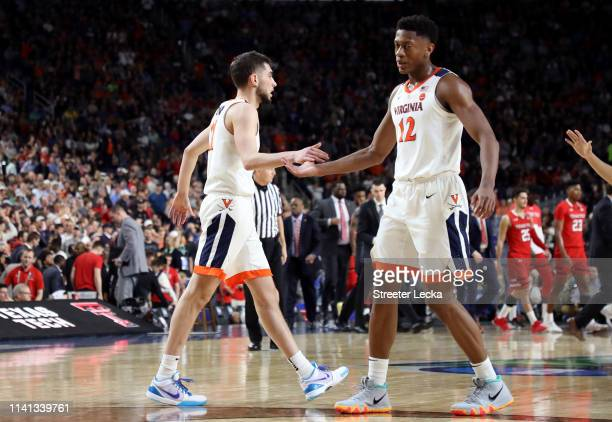 Ty Jerome and De'Andre Hunter of the Virginia Cavaliers celebrate their teams lead in the first half against the Texas Tech Red Raiders during the...