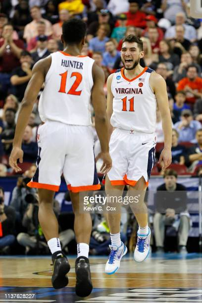 Ty Jerome and De'Andre Hunter of the Virginia Cavaliers react after a play in the second half against the Gardner Webb Runnin Bulldogs during the...