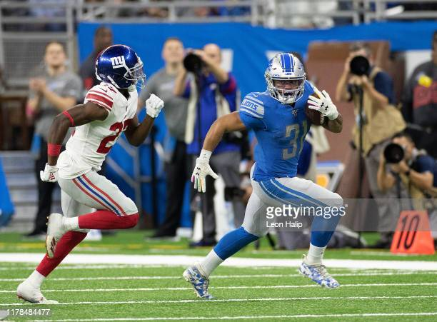 Ty Johnson of the Detroit Lions runs for a first down as Deandre Baker of the New York Giants gives chase during the fourth quarter of the game at...