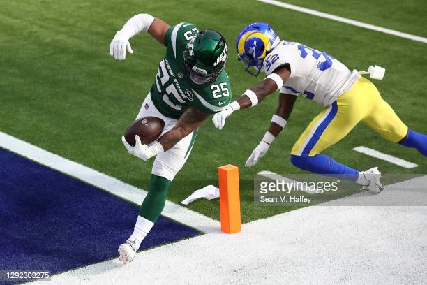 Ty Johnson of the New York Jets rushes for an 18 yard touchdown after a reception ahead of Jordan Fuller of the Los Angeles Rams during the first...