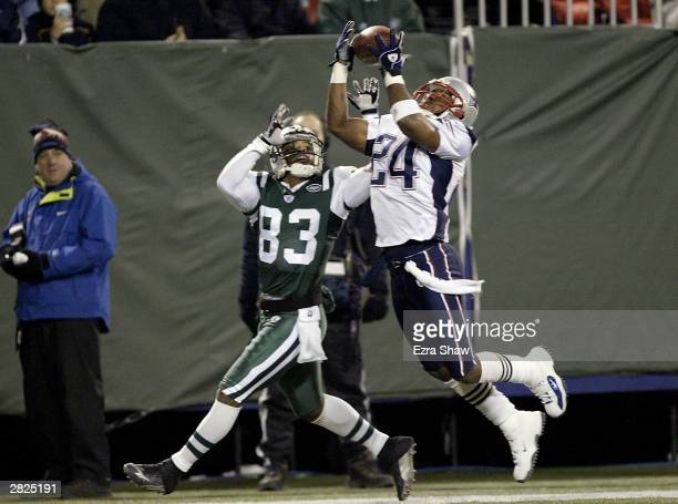 Ty Law of the New England Patriots intercepts a pass intended for Santana Moss of the New York Jets on December 20 2003 at Giant Stadium in East...