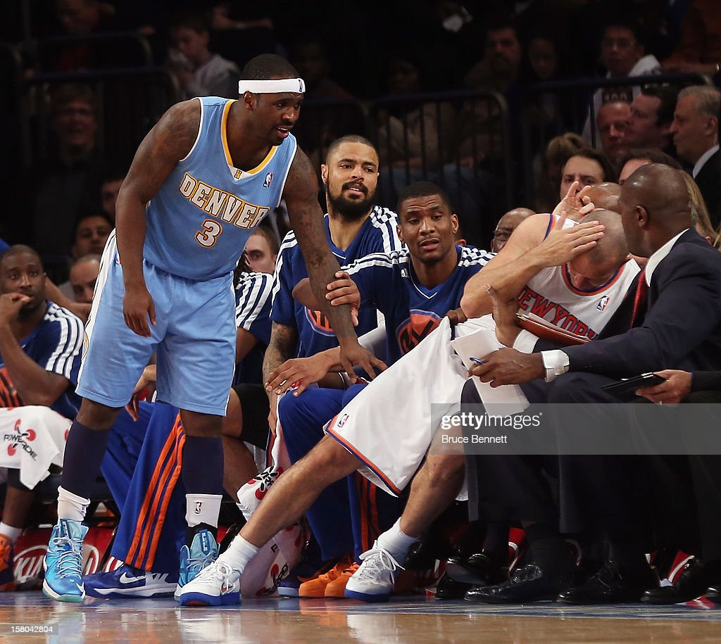 Ty Lawson #3 of the Denver Nuggets hits Jason Kidd #5 of the New York Knicks into the players bench at Madison Square Garden on December 9, 2012 in New York City.