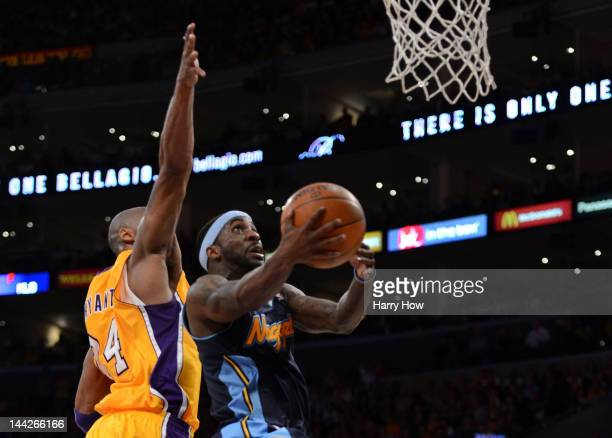 Ty Lawson of the Denver Nuggets lays the ball up in front of Kobe Bryant of the Los Angeles Lakers in the second half in Game Seven of the Western...